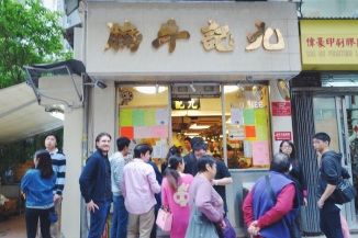 Simon waits in front of Kau Kee Eatery in Hong Kong for the Curry Beef Noddles